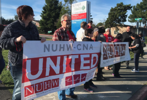 First Ward City Council member Leslie Castellano, NUHW representative and Saint Joseph's employee Alan McCloskey hold banners with others in front of St. Joseph Hospital in Eureka.
