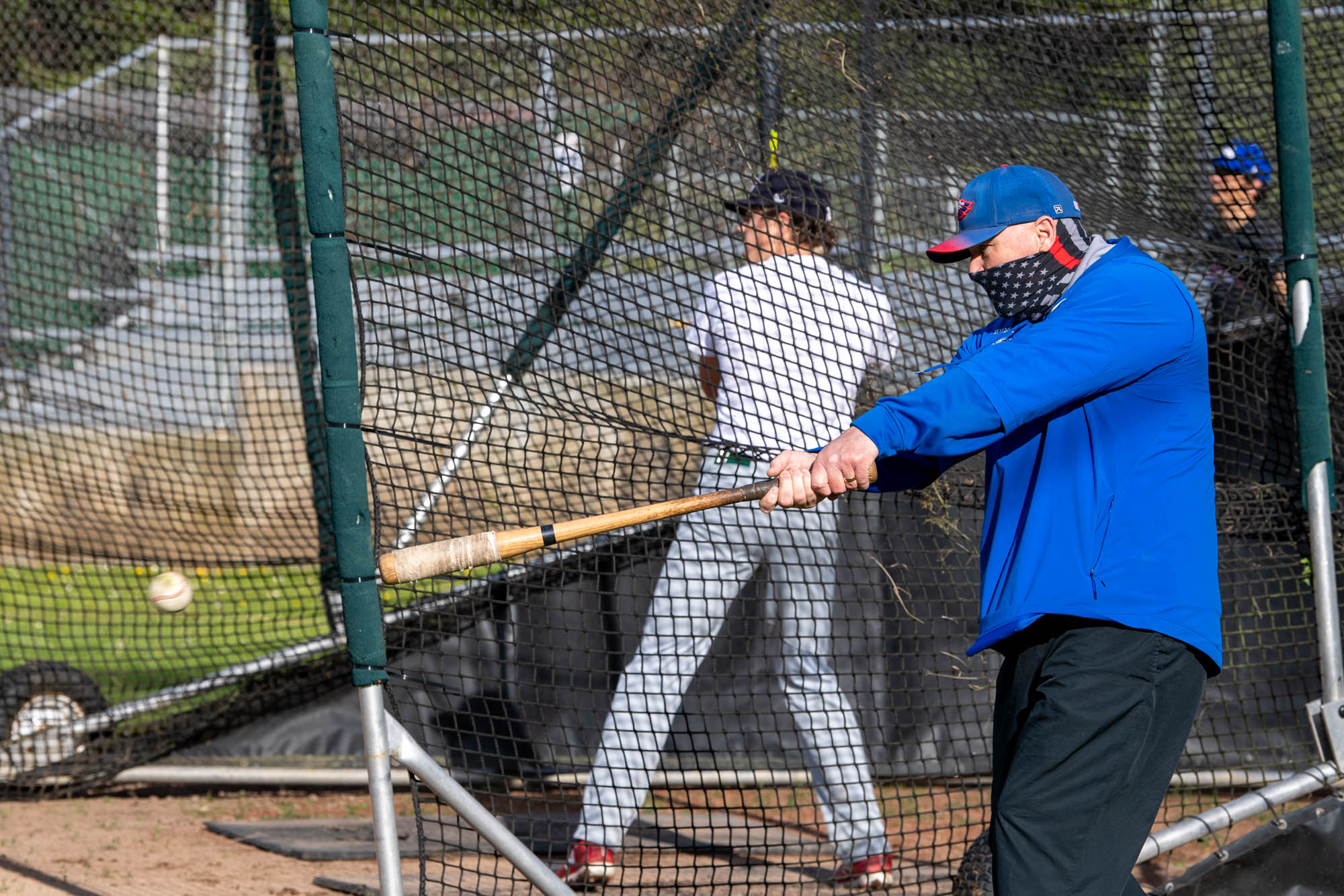 Coach Dan Joyner hits a grounder to the infield during the first day of practice.