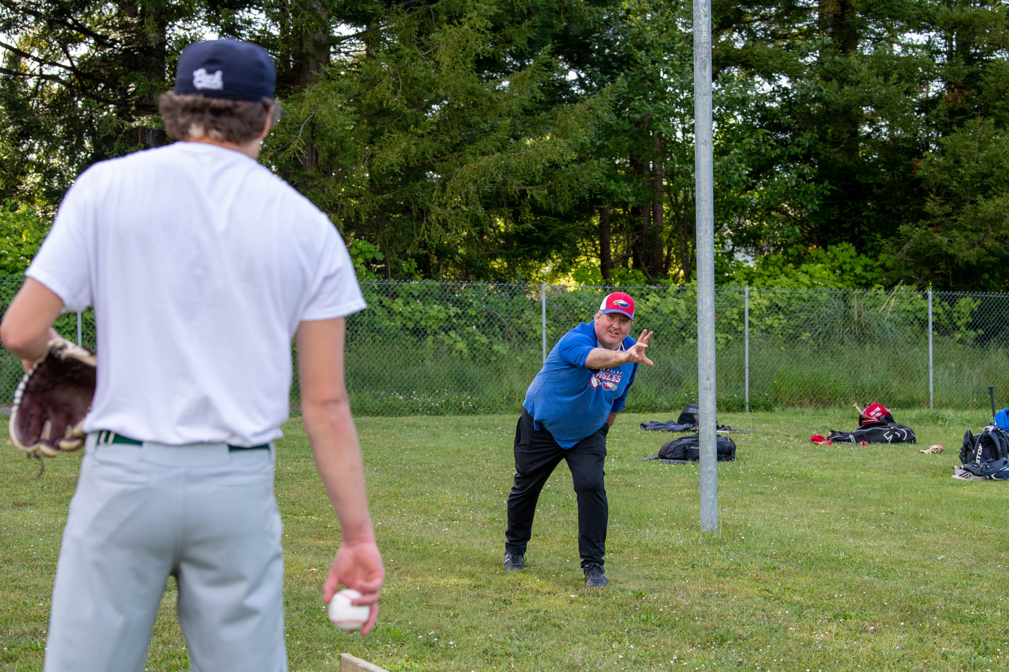 Humboldt Eagles board member Jim Pastori instructs pitcher Hayden Bode to release the ball lower.