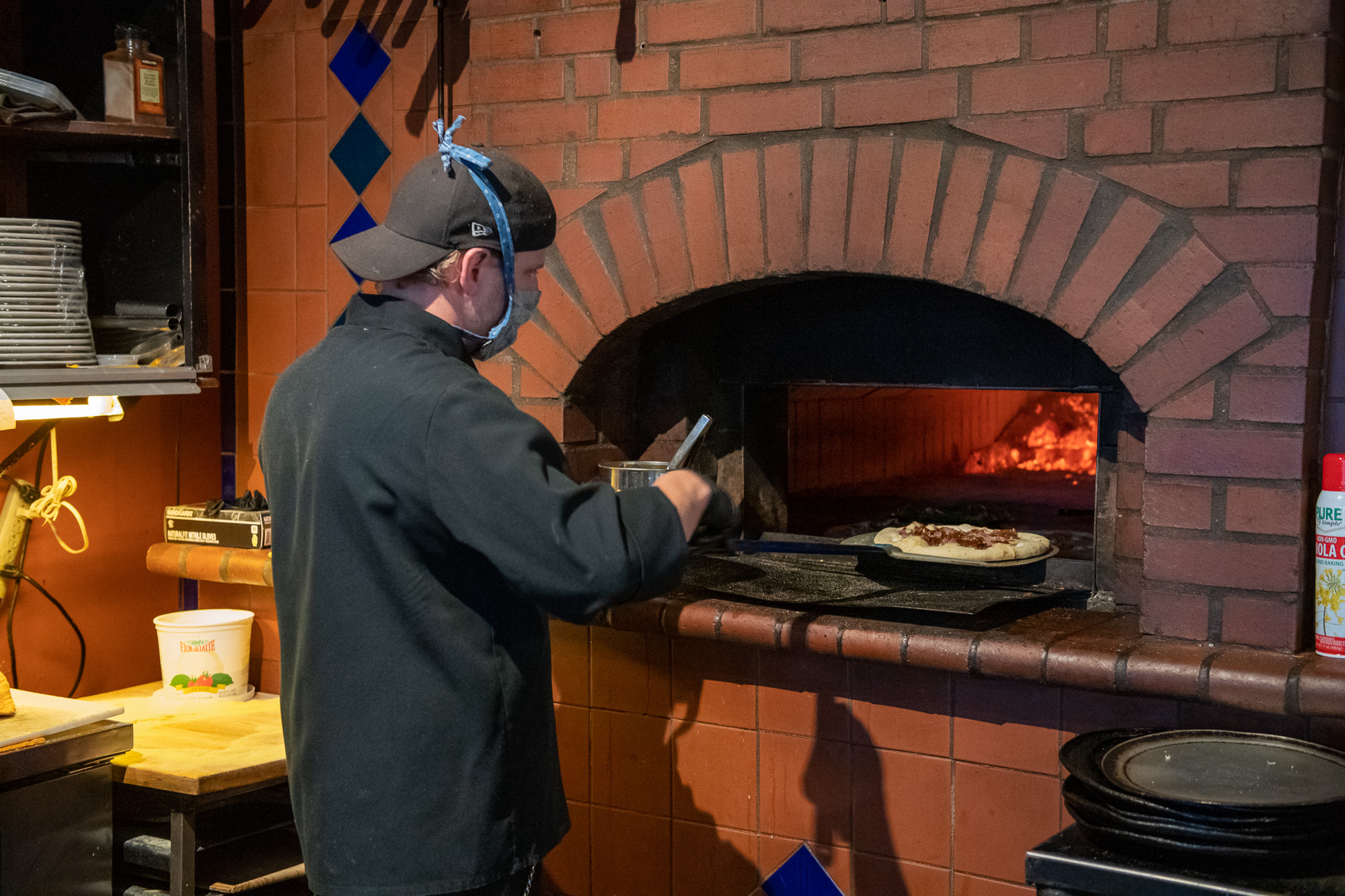 Chef and Manager of Brick and Fire Jeremy Wadlington checks a pizza in the wood fire oven Friday night for a take out order. The restaurant will reopen for dine in service on Wednesday. Wadlington said the restaurant and staff were ready to reopen and really need the people to come back.