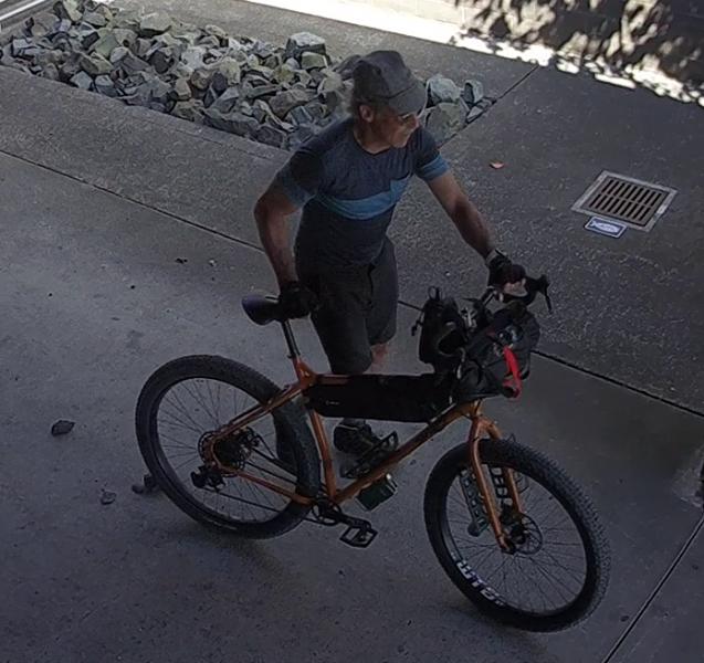 Older man wheeling a bicycle