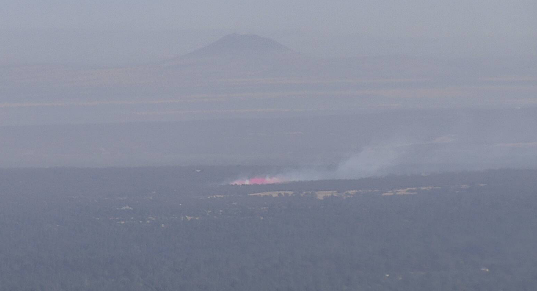 A plane lays down a line of pink retardant on the Orlinda Fire.