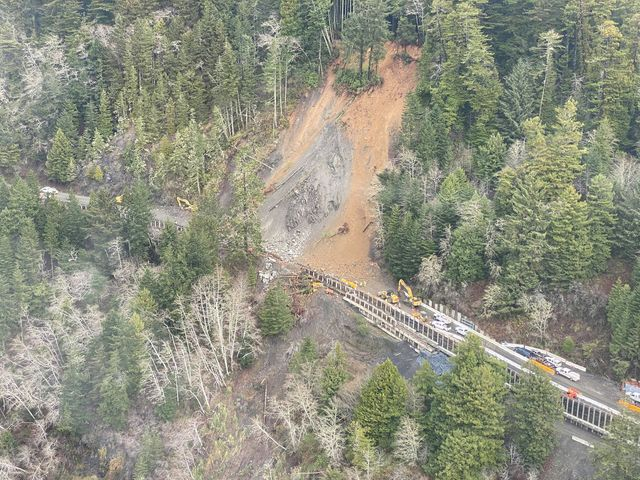Crumpled wooden structures have been pushed over the edge of the roadway by the slide. [Photo from Caleb, a pilot flying the coast today]