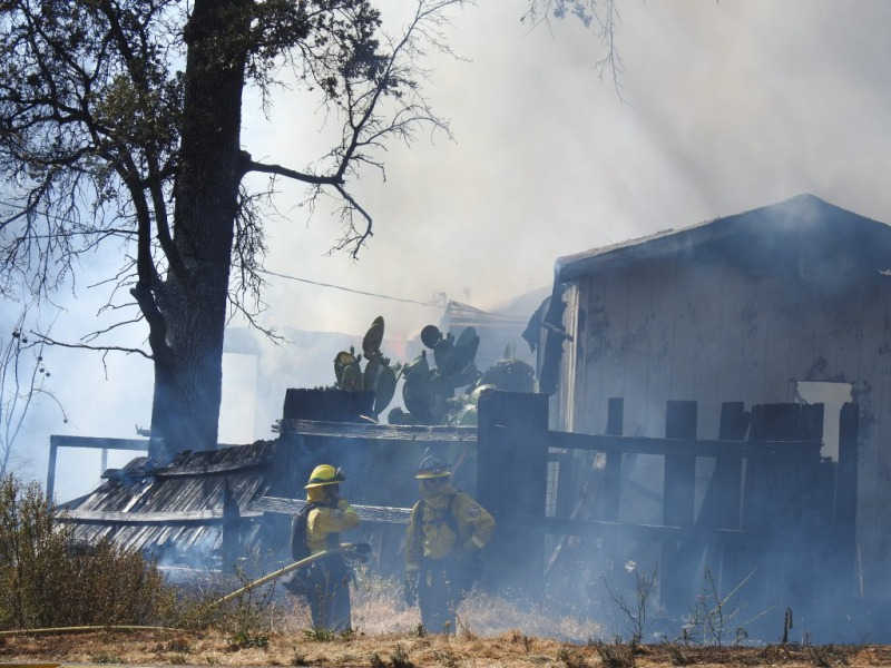 Cal Fire personnel on the perimeter of a burning home